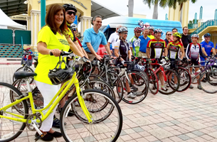 people standing next to their bicycles in front of mizner park amphitheater