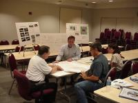 A group of planners sitting at a table inspecting plans, surrounded by posters of plans and photos.